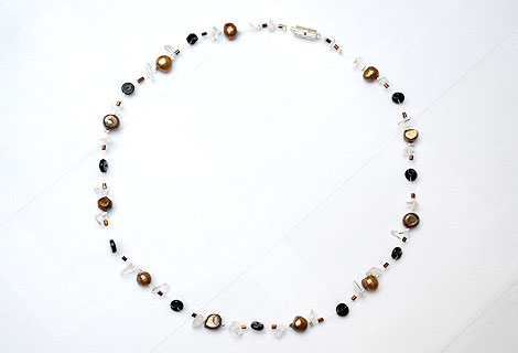 Nicola pearl floating necklace - This exquisite necklace of bronze freshwater pearls, semi-precious gems and disc-shaped black beads floats on your skin and adds a touch of glamour to any outfit. Strung onto clear illusion cord. Magnetic clasp.