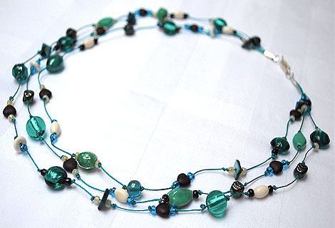 Claire green three-tiered necklace - Beautiful blue green mixed glass and foil beads interspersed with small chocolate brown, heart-shaped beads. Strung and knotted onto dark blue thread.